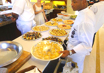 Frank, catering staff for Metro City              Wings Catering, placing down additional platters of hors d'oeuvres for the              P. Diddy's All White 4th of July event.
